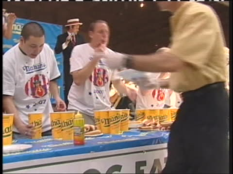 group of men participate in a hot dog eating contest. - spielkandidat stock-videos und b-roll-filmmaterial