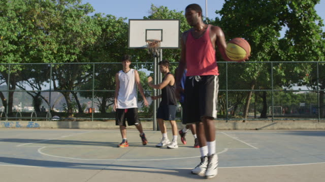 ws a group of men play basketball together / rio de janeiro, brazil - bouncing stock videos & royalty-free footage