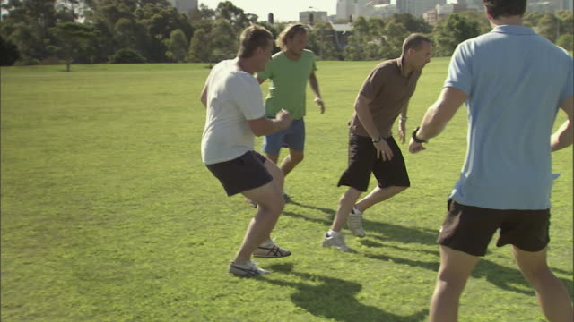 ws, pan, group of men playing soccer in city park, sydney, australia - kicking stock videos & royalty-free footage