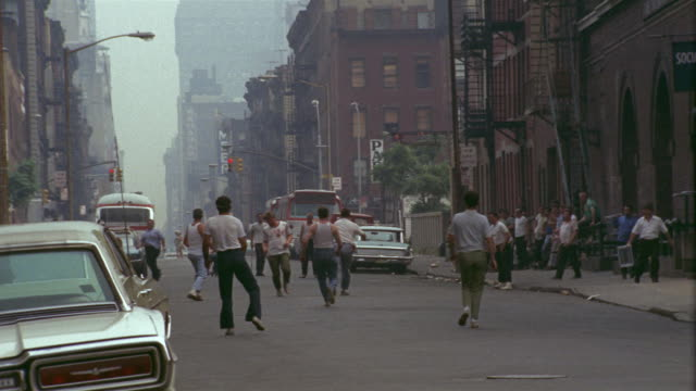 1969 ws group of men playing stickball on city street / manhattan, new york - anno 1969 video stock e b–roll