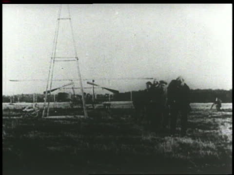 vídeos de stock e filmes b-roll de b/w 1903 group of men pulling early wright brothers' airplane with rope on field - 1903