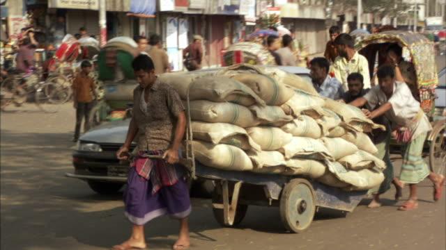 MS, PAN, Group of men pushing cart loaded with stack of sacks on busy street, Dhaka, Bangladesh