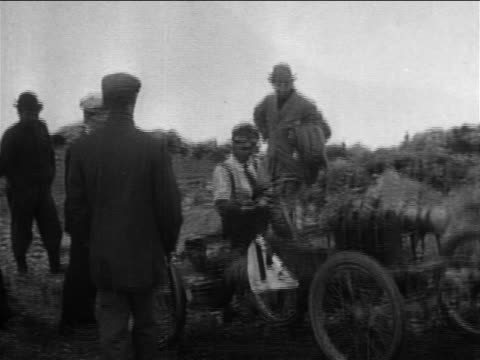 B/W 1905 group of men pushing man in race car up hill in car race on Pike's Peak / documentary