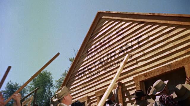 vídeos de stock, filmes e b-roll de ms group of men raising  pre-fabricated front of new building of town - instalando