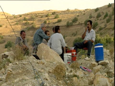 vídeos de stock e filmes b-roll de group of men relaxing on mountain pass/ kurdistan iraq - geleira portátil