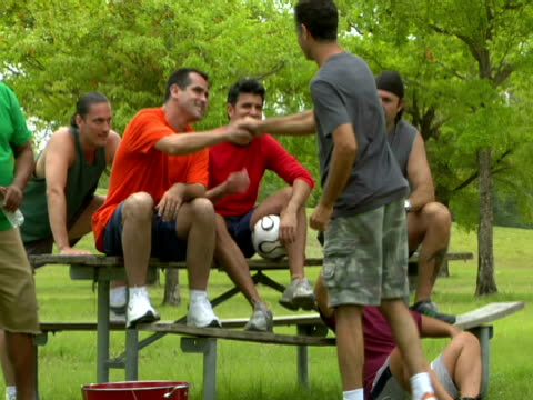 MS,  group of men resting at picnic table after kicking ball in park,  Miami,  Florida,  USA