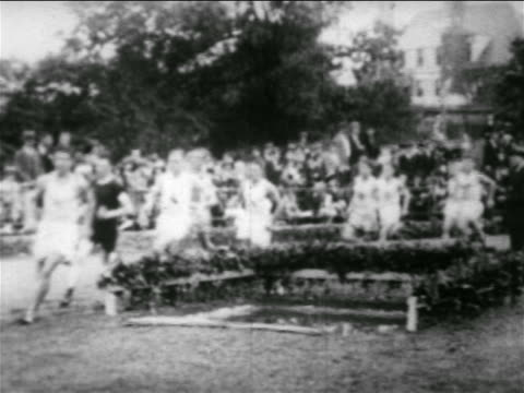 b/w 1930 pan group of men running around track in race / travers island, ny - men's track stock videos and b-roll footage