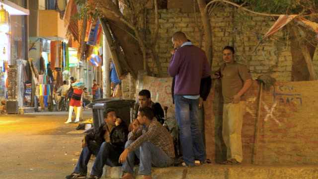 ms group of men sitting while market in background at night / hurghada, red sea coast, egypt - hurghada stock-videos und b-roll-filmmaterial