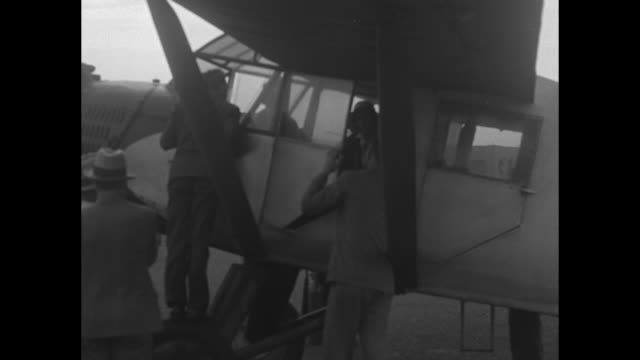 group of men standing next to airplane parked at airport; plane bears aviatrix ruth rowland nichols, injured in new brunswick and en route to new... - start und landebahn stock-videos und b-roll-filmmaterial