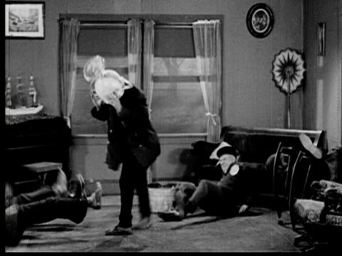 1925 B/W MONTAGE WS Group of men struggling to pull trophy off of man's (Andy Clyde) head and falling to floor / LA WS Man jumping out window with trophy attached / WS Man falling into dirt outside house / Los Angeles County, California, USA