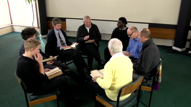 Group of Men studying a book or bible study