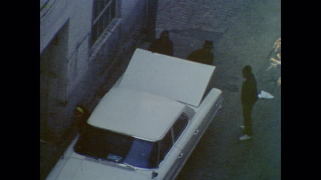 A group of men surround a car as they sneak what appears to be a TV into the trunk before walking away