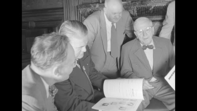 group of men surrounding senator robert taft; he holds paper they seem to be referring to / closer view men conferring / man talking to taft / men /... - surrounding wall点の映像素材/bロール