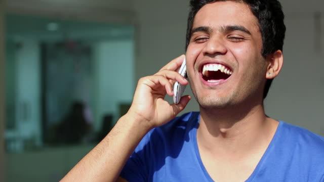 vídeos y material grabado en eventos de stock de group of men talking on a mobile phone - perilla