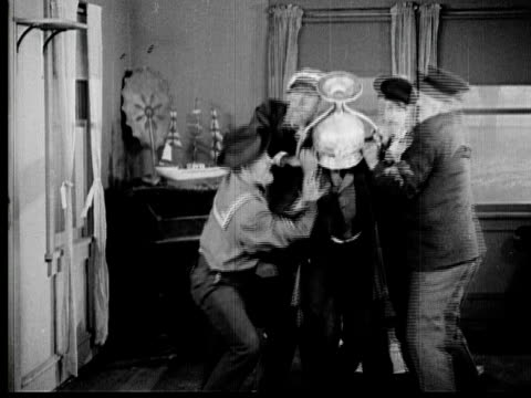 1925 B/W WS Group of men trying to remove trophy off man's (Andy Clyde) head by lifting him up / Los Angeles County, California, USA
