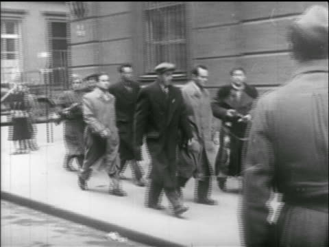 group of men walk on sidewalk / one with rifle / hungarian uprising - 1956 stock-videos und b-roll-filmmaterial
