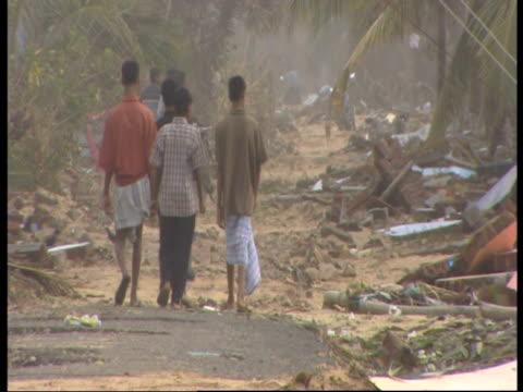 A group of men walk through the rubble of Mullaitivu following the 2004 Indian Ocean Tsunami