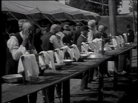 group of men washing their faces in bowls outside a tent / men sitting together on a bench - french overseas territory stock videos & royalty-free footage