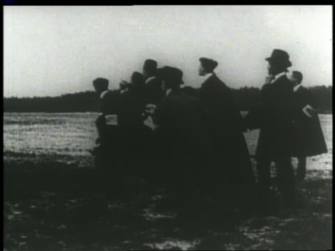 vídeos de stock e filmes b-roll de view group of men watching as wright brothers airplane starts on airfield - 1903