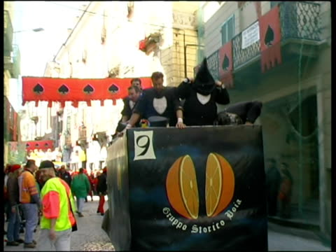 ms zi group of men wearing costumes, riding on horse cart through city street during ivrea festival / ivrea, torino, italy / audio - フロート車点の映像素材/bロール