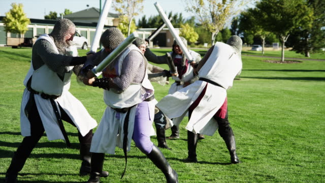 MS Group of men wearing historical clothing fighting with swords in park / Orem,Utah,USA