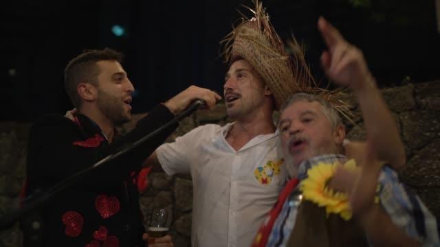 vídeos de stock, filmes e b-roll de grupo de homens que desgastam o traje e o canto do partido de junho durante um partido do junina - microfone