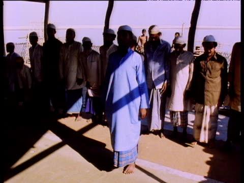 group of men wearing traditional muslim dress kneeling and praying inside hut - 僧衣点の映像素材/bロール