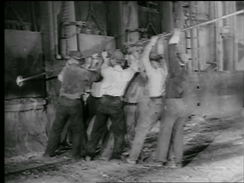 b/w 1942/43 group of men working together to push large pole into furnace in steel mill / newsreel - acciaieria video stock e b–roll