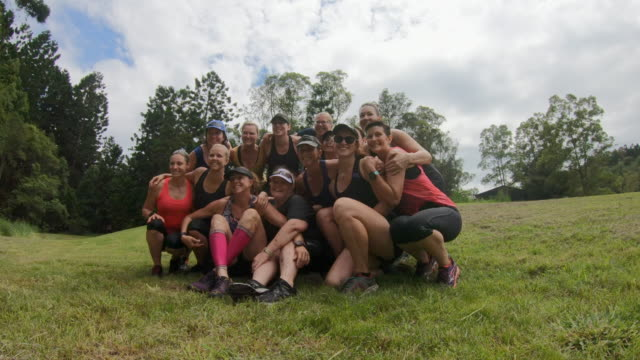 group of middle aged sports women gathering for a group photo after competing in a cross country fun run - mischief stock videos & royalty-free footage