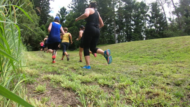 Group of Middle Aged Women Running in a Cross Country Obstacle Course Muddy Fun Run
