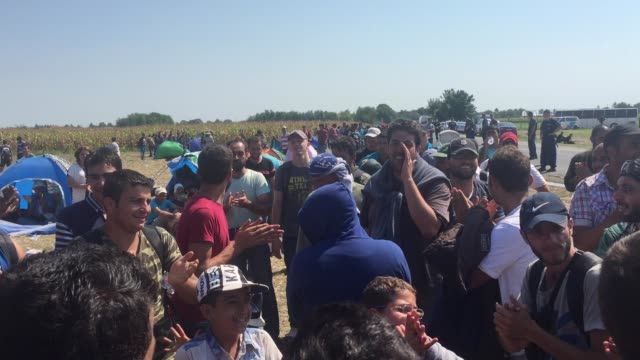 A group of migrants sing as they wait for buses to take them to a registration centre after they had crossed the border from Serbia into Hungary...