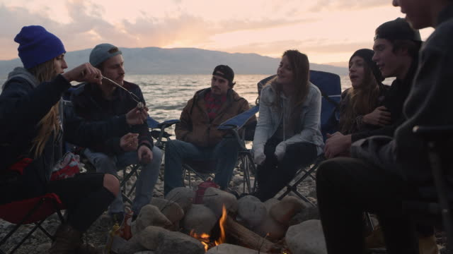 vidéos et rushes de group of millenials gathered around campfire at sunset - histoire