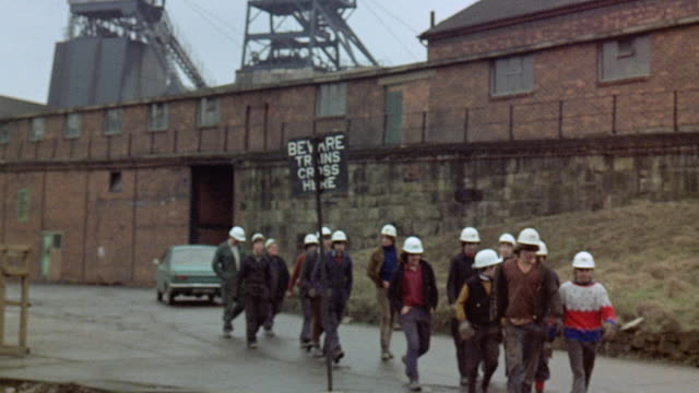 1971 ts group of miners walking outside at a plant / united kingdom - 1971 stock-videos und b-roll-filmmaterial