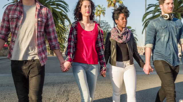 Group of mixed race friends holding hands outdoors