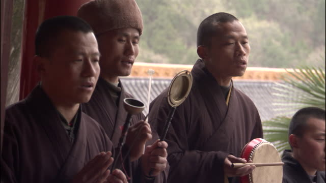 MS Group of monks burning incense and playing instruments at Fawang Shaolin Temple shrine / Monk praying / Henan Provine, China