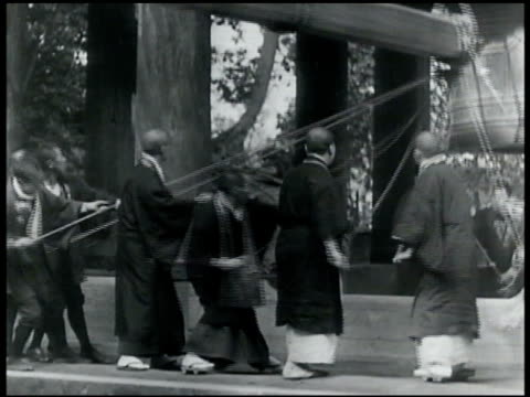 vidéos et rushes de celebration group of monks ringing giant bell in kyoto's chionin temple - 1935