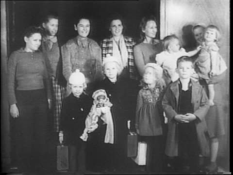 a group of mothers and their children pose for camera as american refugees from singapore and rangoon / close up of a young girl in a white cap /... - bow pose stock videos & royalty-free footage