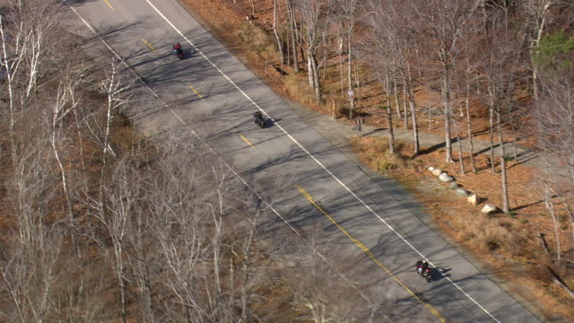 vídeos de stock e filmes b-roll de ms aerial ts zo tu group of motorcyclist moving on highway through forest area at crawford notch / new hampshire, united states - three people