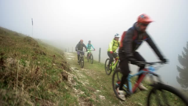 group of mountain bikers riding down a mountain trail in fog - mountain biking stock videos & royalty-free footage