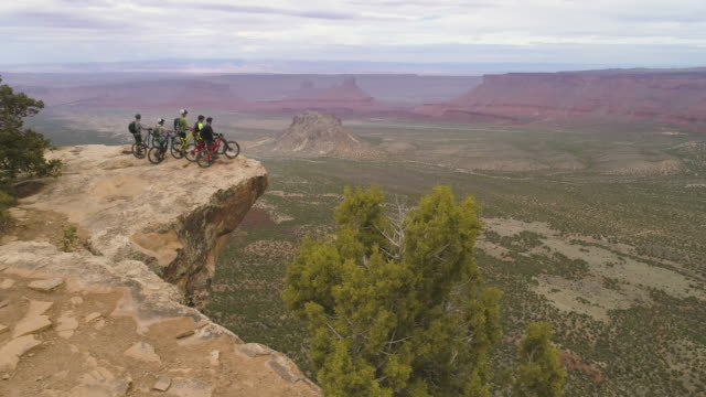 a group of mountain bikers riding through the famous slick rock trails of moab. - moab utah stock-videos und b-roll-filmmaterial