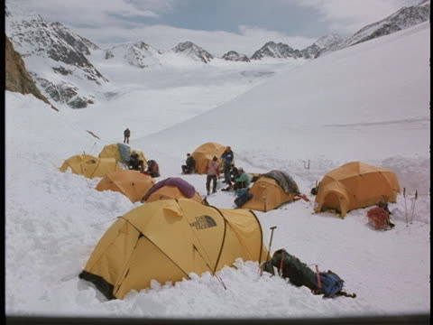 a group of mountain climbers rest at camp in a snowy valley. - base camp stock videos & royalty-free footage