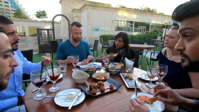 vidéos et rushes de groupe d'amis arabes multi-ethniques déjeuner dans un restaurant à dubaï - multi ethnic group