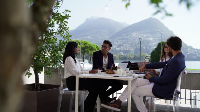 group of multi ethnic business men and women meeting out outdoor restaurant - meeting stock videos & royalty-free footage