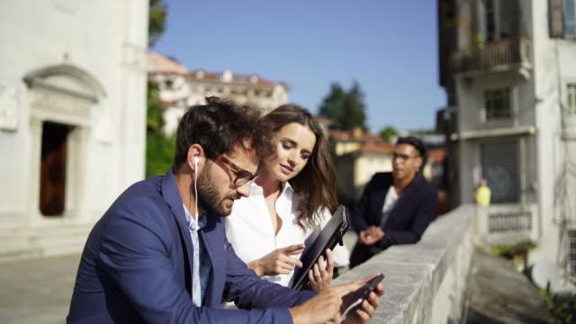 vidéos et rushes de group of multi ethnic business people using smartphones talking on lookout over city - lunette soleil
