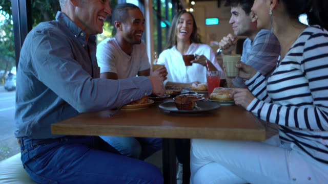 group of multi ethnic friends enjoying breakfast with sweet pastry, coffee and juice talking and having a nice time - french food stock videos & royalty-free footage