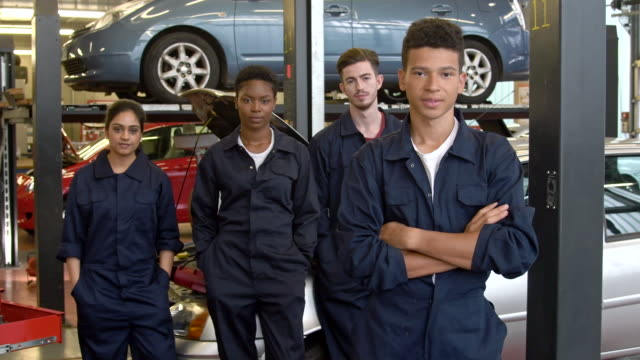 Group of multi racial college apprentices in car workshop wearing boiler suits