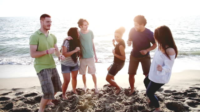 Group of multi-ethnic friends dancing on the beach