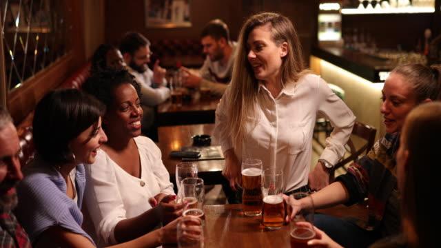 gruppe von multiethnischen freunden, die eine gute zeit zusammen in einer bar haben - pint stock-videos und b-roll-filmmaterial