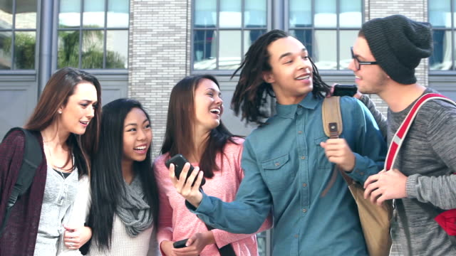 Group of multi-ethnic students gather round mobile phone