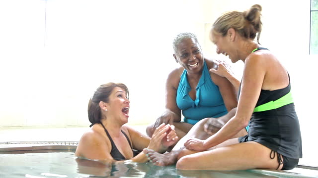 Group of multi-ethnic women talking by side of pool